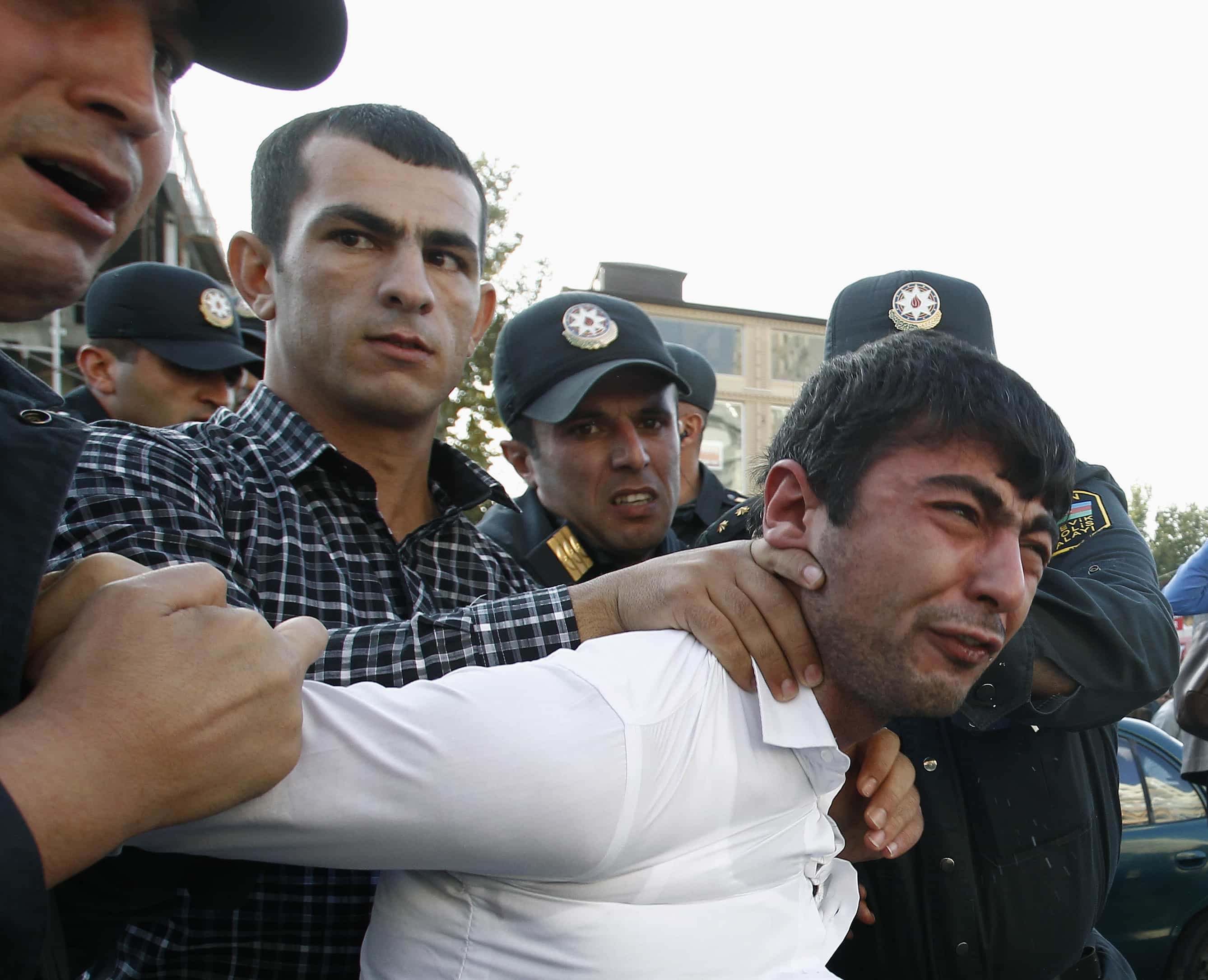 Police detain an opposition supporter in Baku, 12 October 2013, REUTERS/David Mdzinarishvili
