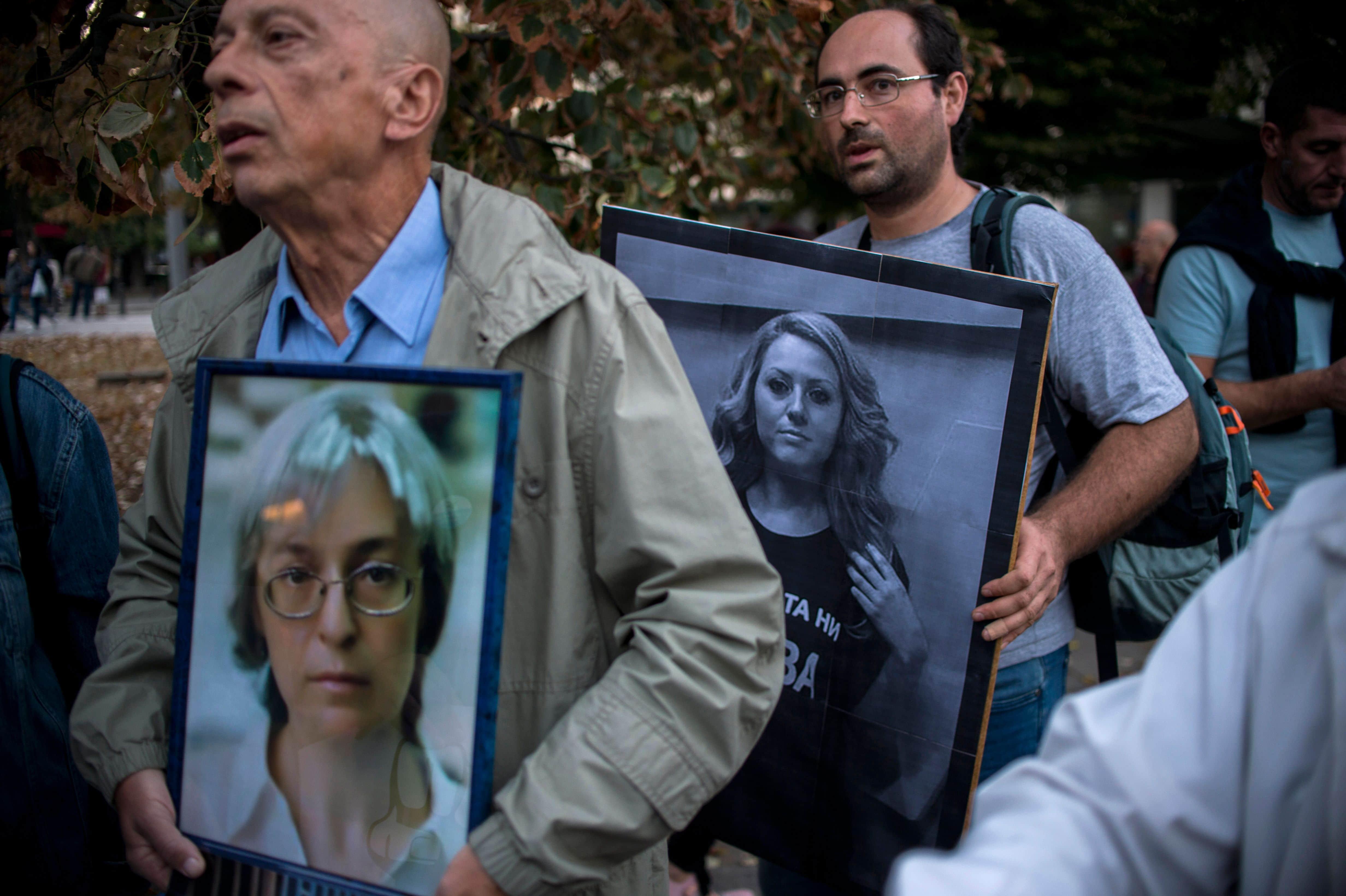 Two men hold pictures of murdered Bulgarian journalist Viktoria Marinova (C) and murdered Russian journalist Anna Politkovskaya (L), during a vigil in Sofia, Bulgaria, 8 October 2018, NIKOLAY DOYCHINOV/AFP/Getty Images