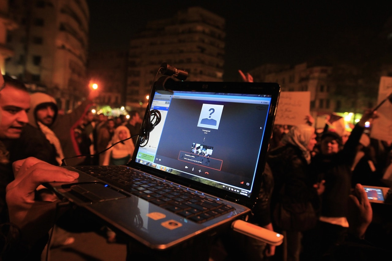 An Egyptian protester streams a demonstration via Skype as people gather in Cairo's Tahrir Square, 20 December 2011, MOHAMMED ABED/AFP/Getty Images