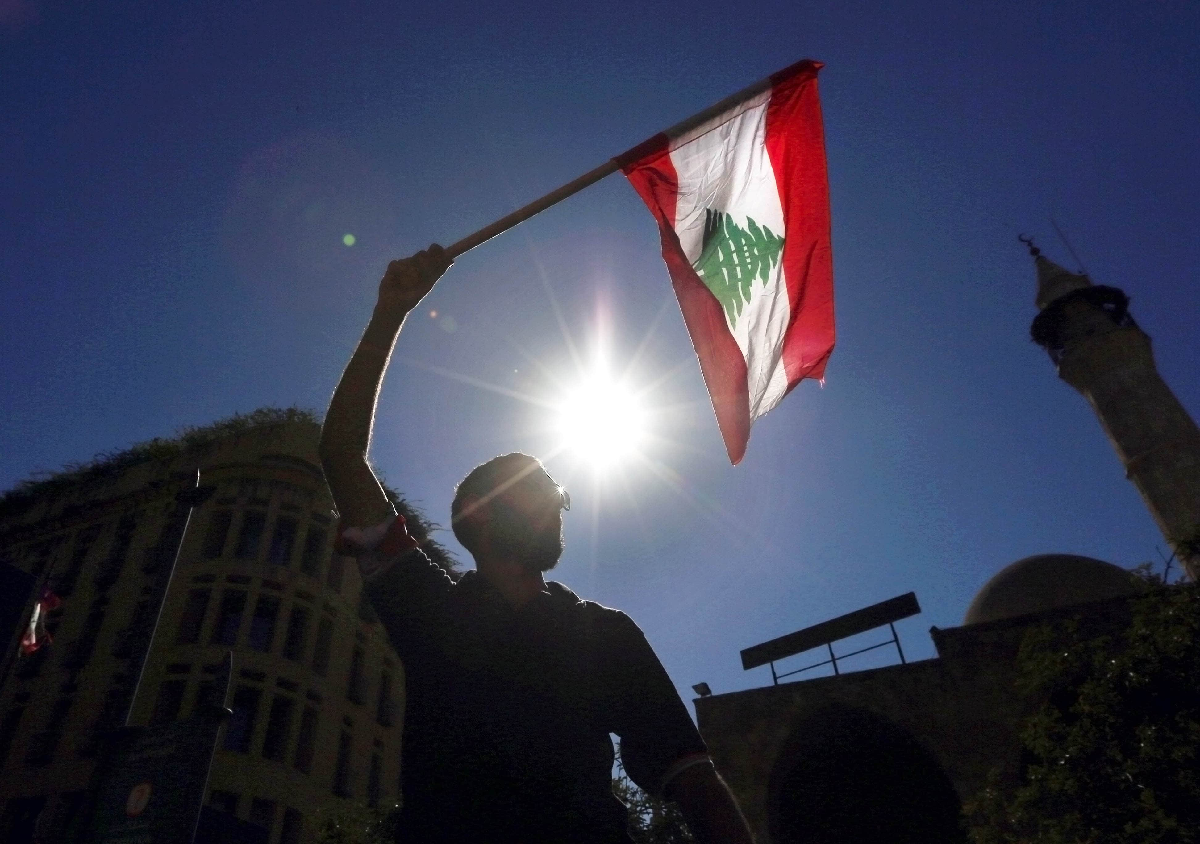 A man waves a Lebanese flag during a protest near the parliament building in downtown Beirut, Lebanon, AP Photo/Bilal Hussein