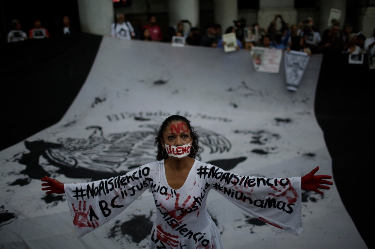 A woman wearing a dress that reads 'no to silence' stands in front of a flag during a demonstration to end violence against journalists in Mexico at the Interior Ministry in Mexico City, 15 June 2017, Miguel Tovar/LatinContent/Getty Images