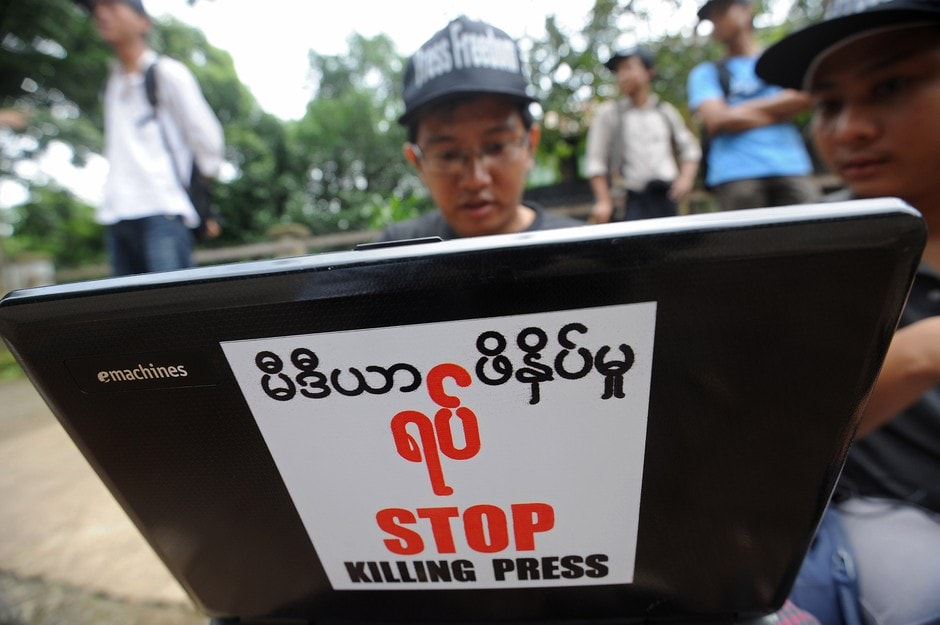 A Burmese journalist works on his laptop carrying a sticker reading 'Stop Killing Press' as he waits outside a court for a ruling on a defamation case against The Voice Weekly in Yangon, Burma, on 23 August 2012., AFP/Soe Than Win