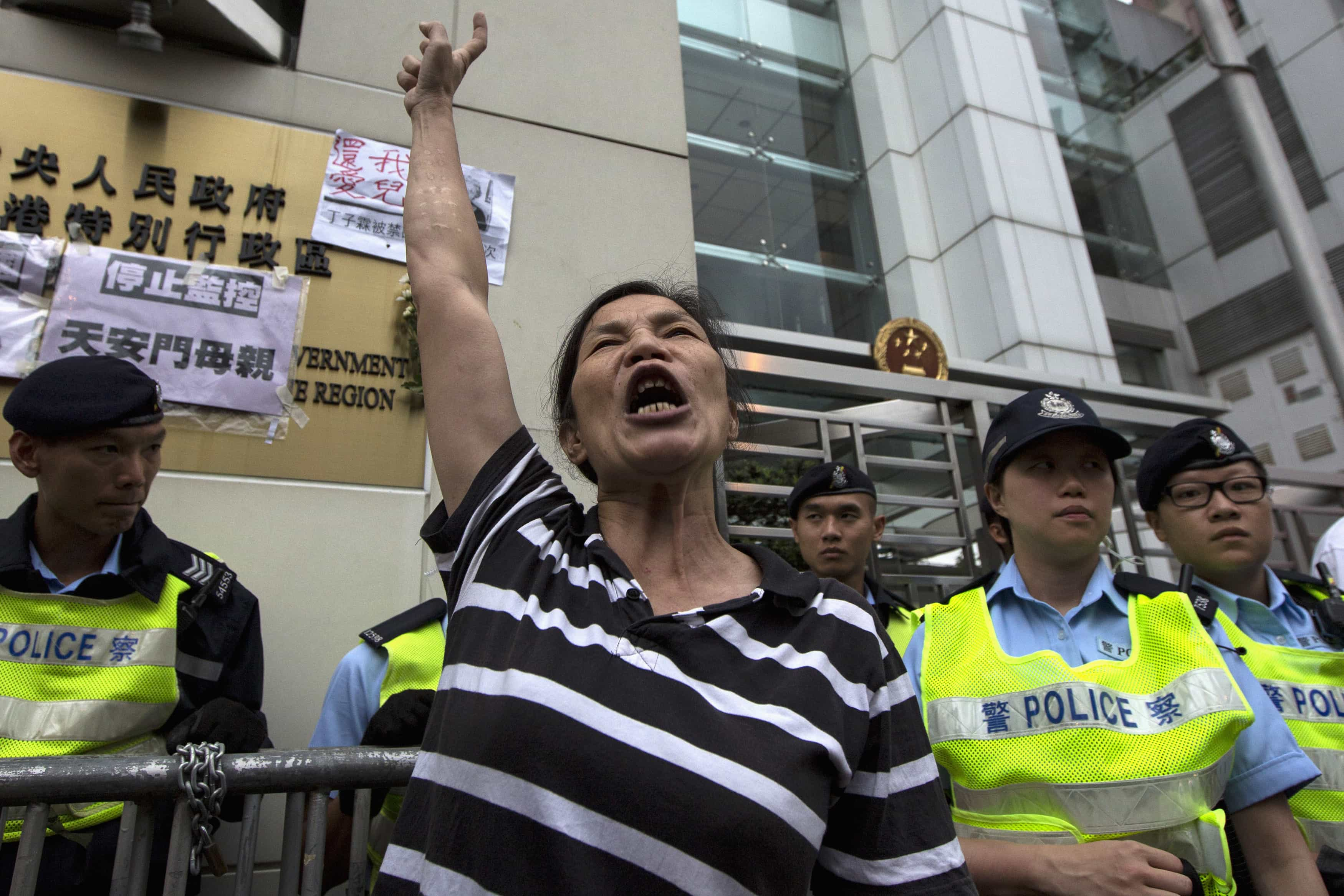 Pro-democracy activist Lui Yuk-lin shouts during a protest calling for the release of Chinese journalist Gao Yu, Hong Kong publisher Yao Wentian and Chinese lawyer Pu Zhiqiang, outside the Chinese liaison office in Hong Kong on 11 May 2014, REUTERS/Tyrone Siu