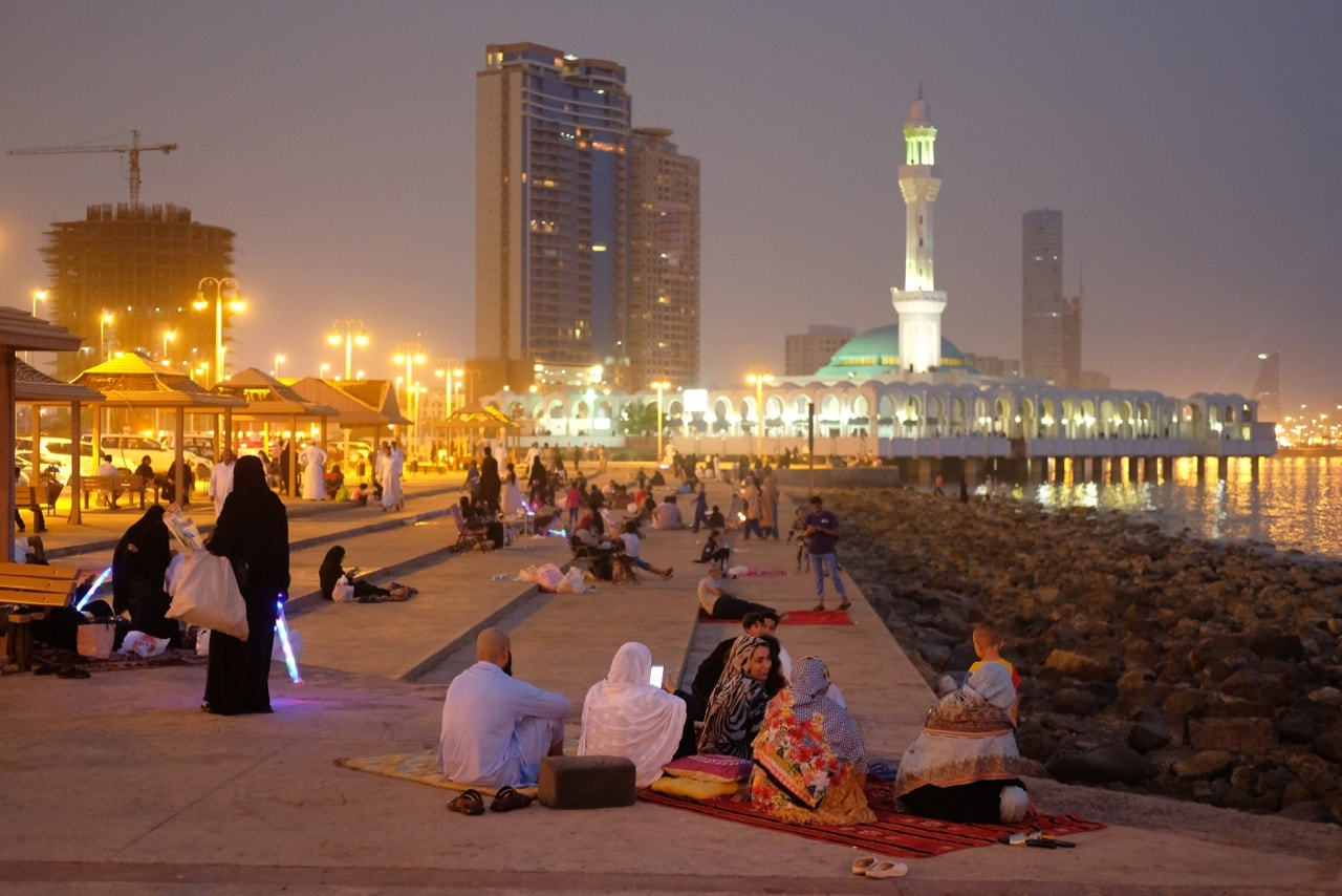 People sit along the Corniche waterfront with the Al Rahma mosque in the background in Jeddah, Saudi Arabia, 22 June 2018, Sean Gallup/Getty Images
