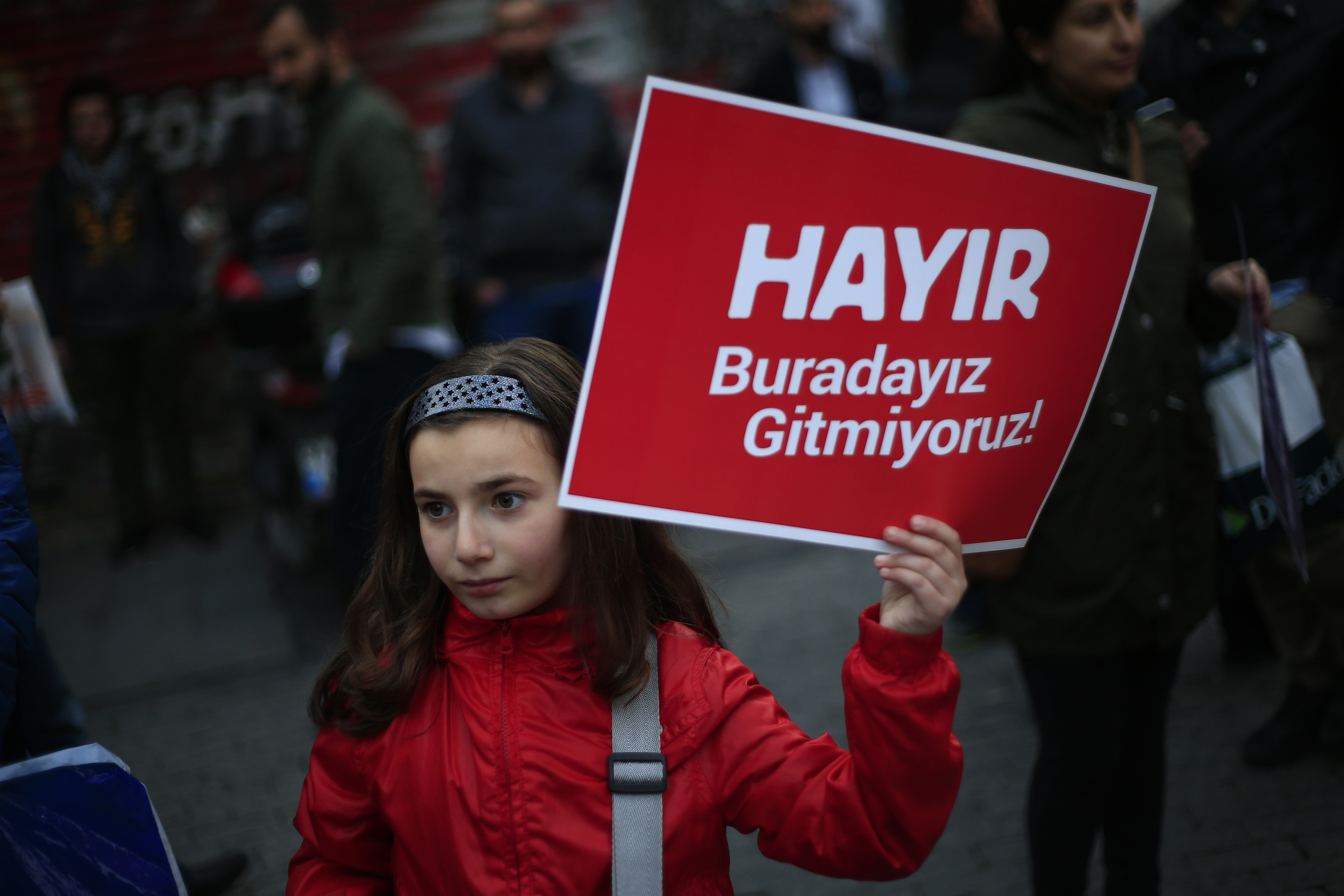 A girl holds a placard that reads: 'NO, we are here, we are not going anywhere', during a protest by supporters of the 'NO' vote against the referendum outcome, in Istanbul, 21 April 2017, AP Photo/Lefteris Pitarakis