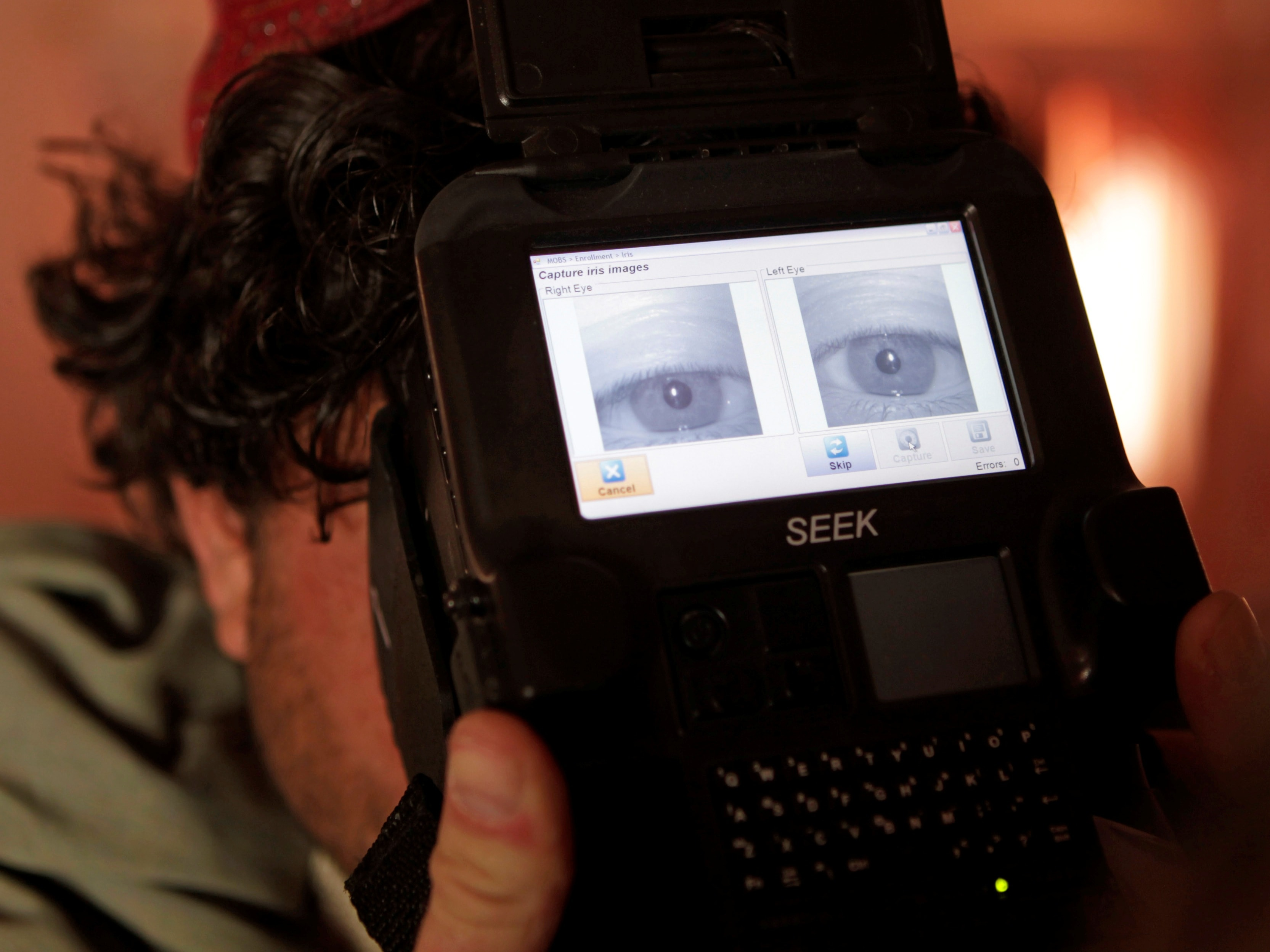 A US Army soldier takes a biometric scan of an Afghan police officer before paying his monthly salary, in Kandahar province, Afghanistan, October 2012, REUTERS/Erik De Castro