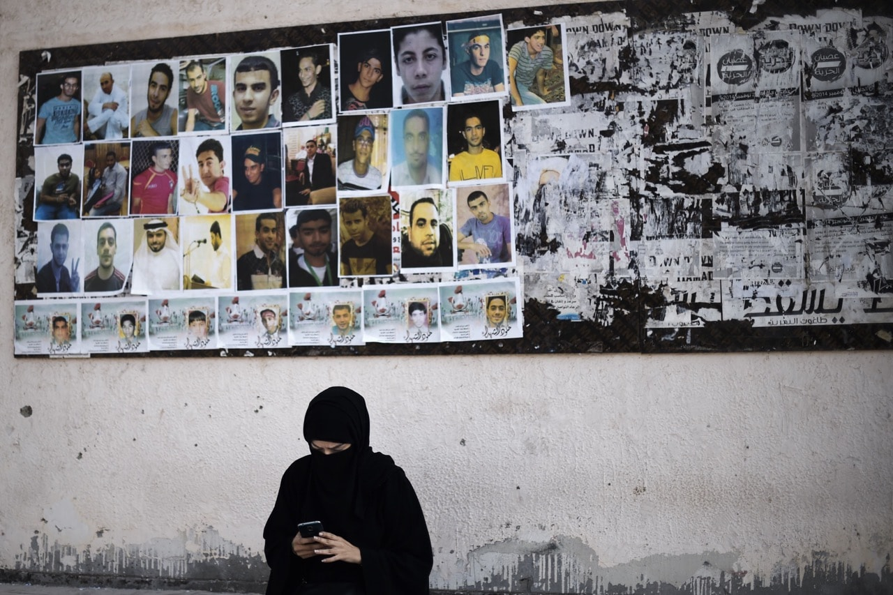 A woman sits near portraits of jailed political activists and protesters killed during clashes with police, before taking part in a demonstration to mark the fifth anniversary of the Arab Spring-inspired uprising in the village of Sitra, Bahrain, 12 February 2016, MOHAMMED AL-SHAIKH/AFP/Getty Images