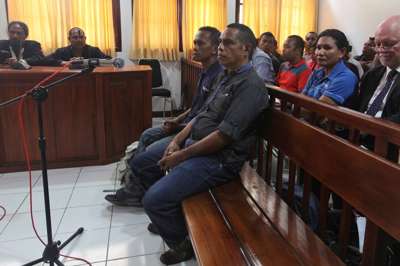 Journalists Lourenco Martins, center front, and Raimundos Oki, center rear, sit on the dock during their trial at a court in Dili, East Timor, 1 June 2017, AP Photo/Kandhi Barnez