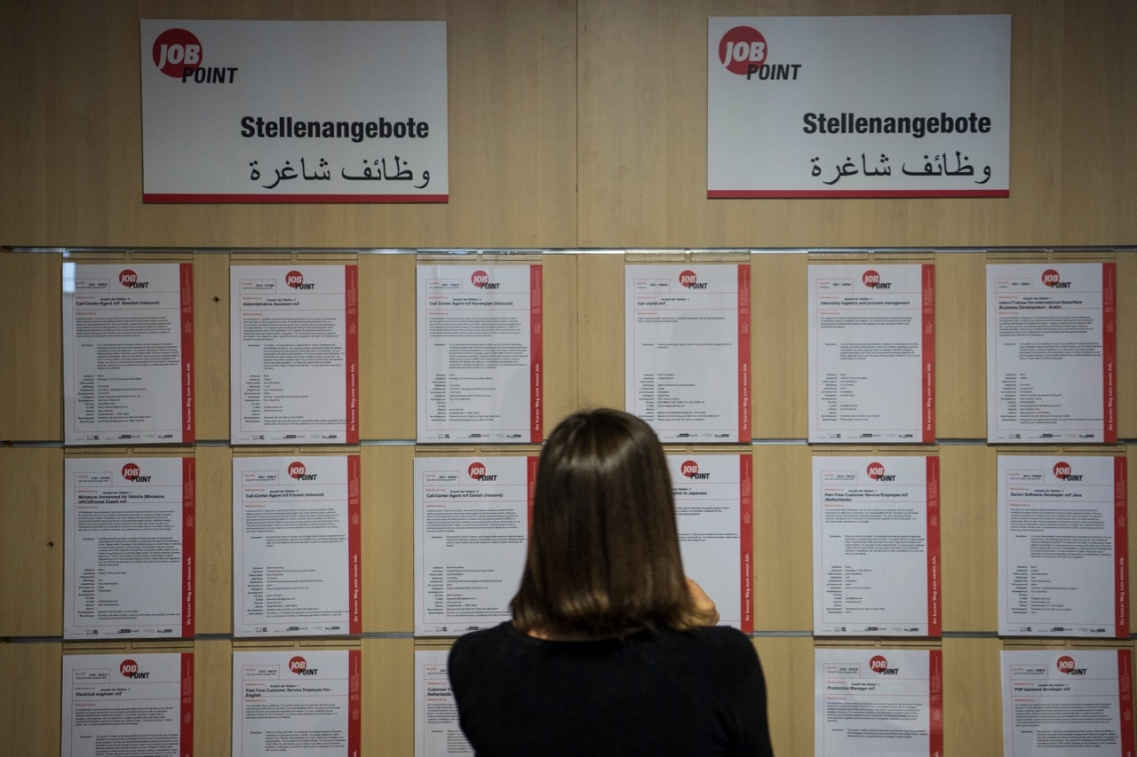 A journalist looks at job offers during the inauguration of a new jobs counseling center for migrants and refugees at the former Tempelhof Airport in Berlin, 27 January 2016 , JOHN MACDOUGALL/AFP/Getty Images