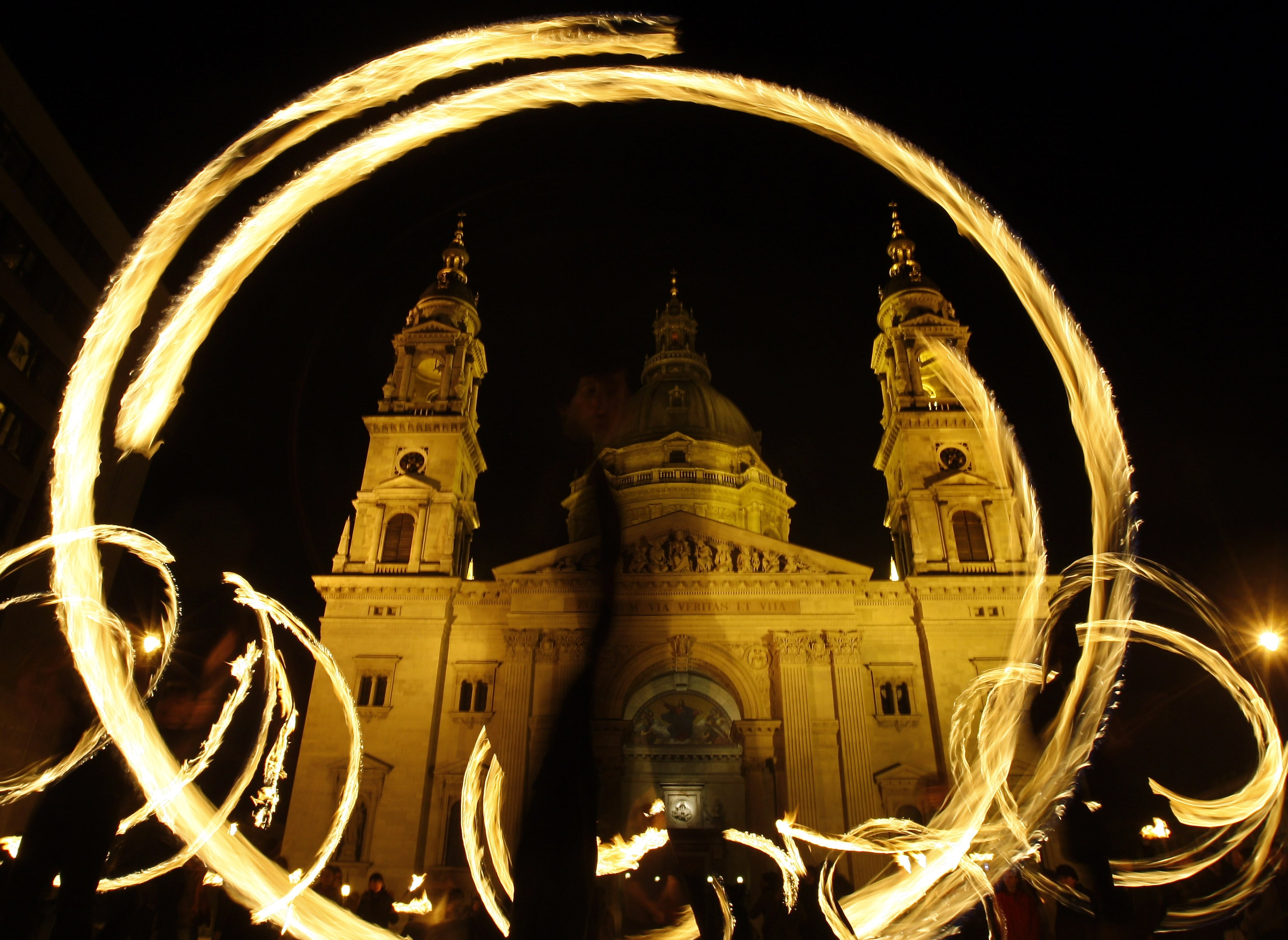 Fire acrobats perform during a gathering to celebrate peace in front of the Main Cathedral in Budapest, 21 March 2009, REUTERS/Karoly Arvai