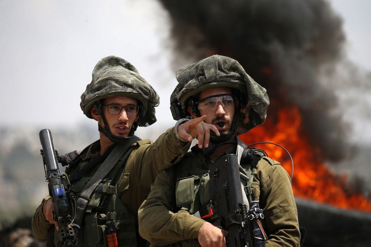 Israeli soldiers talk during clashes with Palestinian protesters in the village of Kfar Qaddum, near Nablus in the occupied West Bank, 1 June 2018, JAAFAR ASHTIYEH/AFP/Getty Images