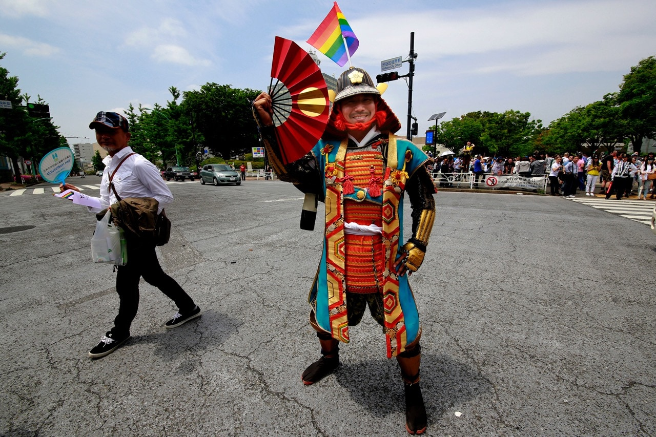 A participant dressed in an ancient samurai warrior costume with the rainbow flag on his helmet poses before the Tokyo Rainbow Pride parade, 7 May 2017, AP Photo/Shizuo Kambayashi