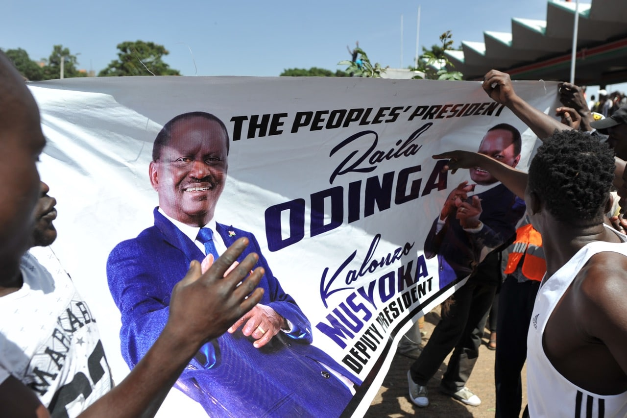 Supporters of the Kenyan opposition coalition leader Raila Odinga hold a banner with his portrait as he prepares to have himself sworn in as the 'people's president' in Nairobi, 30 January 2018, TONY KARUMBA/AFP/Getty Images