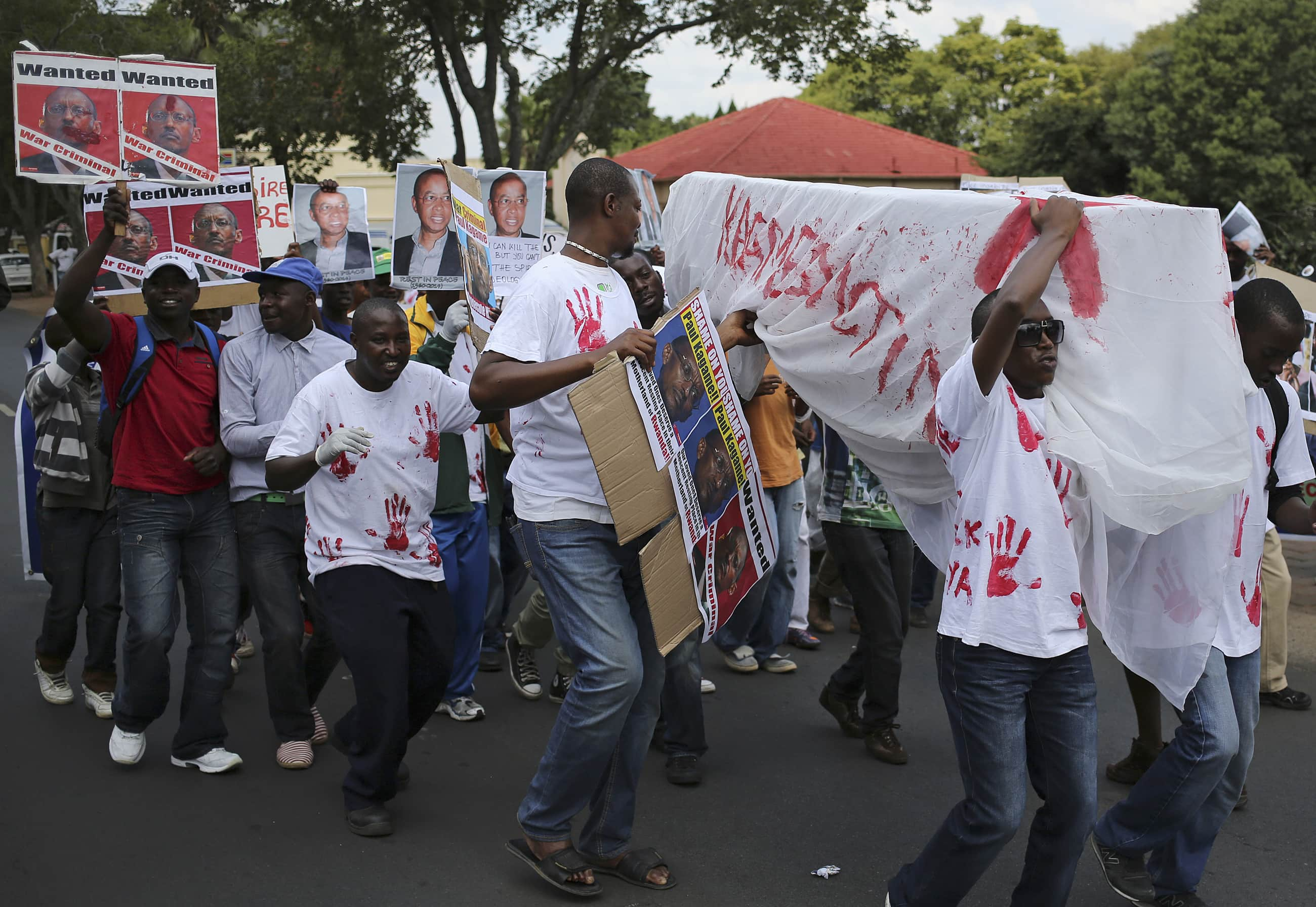 Supporters of the Rwanda National Congress, an opposition party that exiled former Rwandan intelligence chief Patrick Karegeya helped formed in 2011, carry a makeshift coffin as they protest outside the Rwandan embassy in Pretoria after Karegeya was found murdered in a Johannesburg hotel room, 9 January 2014., REUTERS/Siphiwe Sibeko