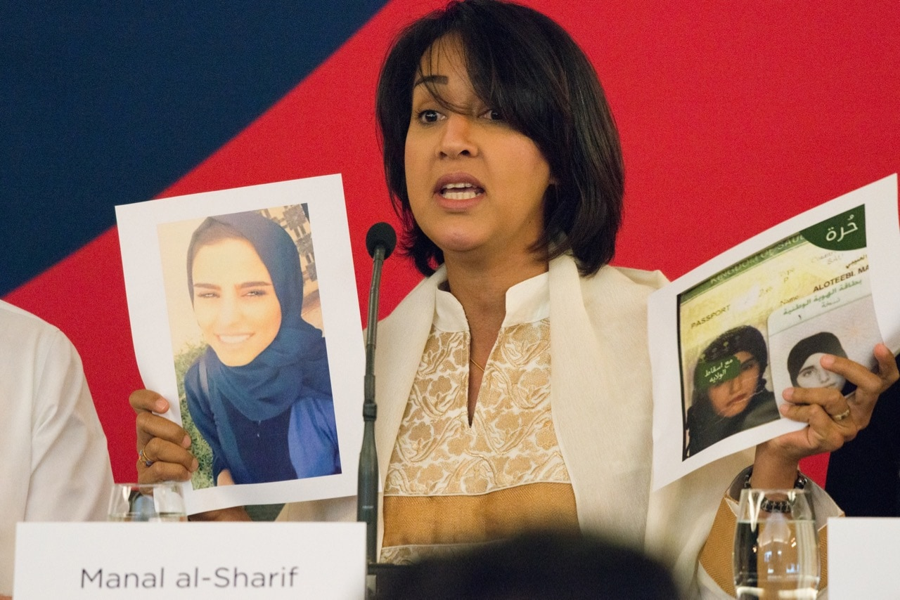 Saudi Arabian activist Manal al-Sharif, who started the #women2drive movement, holds up photos of Mariam al-Otaibi and Alaa Alanazi at the opening of the Oslo Freedom Forum, 22 May 2017, Julia Reinhart/NurPhoto via Getty Images
