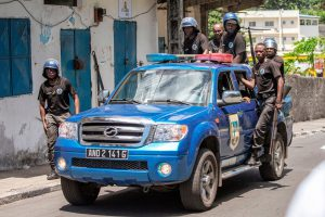 Comoros Gendarmerie officers stand on the back of a car as they disperse opposition supporters, in Moroni, 25 March 2019, GIANLUIGI GUERCIA/AFP/Getty Images