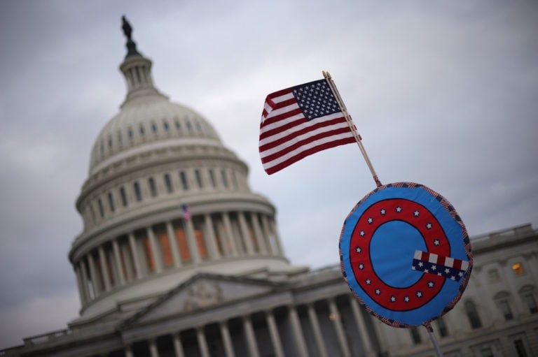 Supporters of former U.S. President Donald Trump fly a flag with a symbol from the group QAnon as they gather outside the U.S. Capitol on the day of the riot, Washington, DC., 6 January 2021, Win McNamee/Getty Images