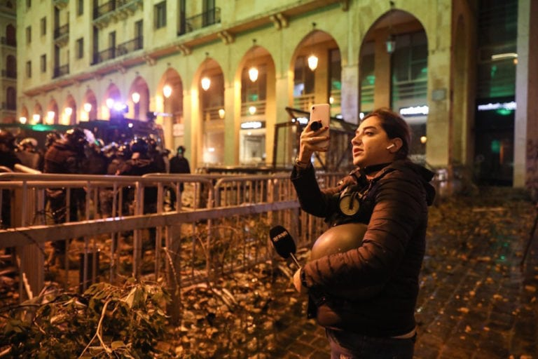 During a protest, a reporter uses a cell phone to film the scene by a security forces' barricade near the parliament, Beirut, Lebanon, 18 January 2020, ANWAR AMRO/AFP via Getty Images