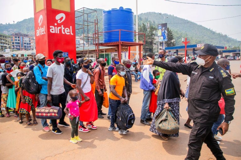 During a lockdown due to COVID-19, a police officer guides people waiting at a bus station in Kigali, Rwanda, 19 January 2021, Xinhua/Cyril Ndegeya via Getty Images