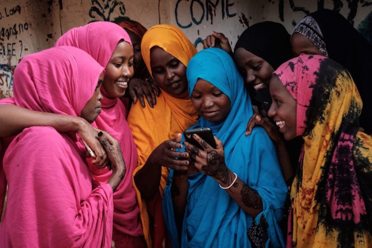 Young Somali refugee women look at a smartphone as they huddle together at the Dadaab refugee camp, in the north-east of Kenya, 16 April 2018, YASUYOSHI CHIBA/AFP via Getty Images