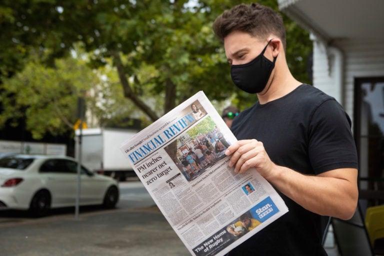 A man wearing a mask reads a newspaper, in Perth, Australia, 2 February 2021, Matt Jelonek/Getty Images