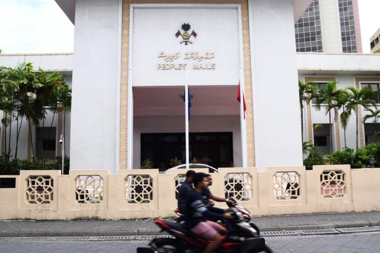 Motorists ride along a street outside the People's Majlis or the Maldives parliament, in Male, 7 February 2018, STR/AFP via Getty Images