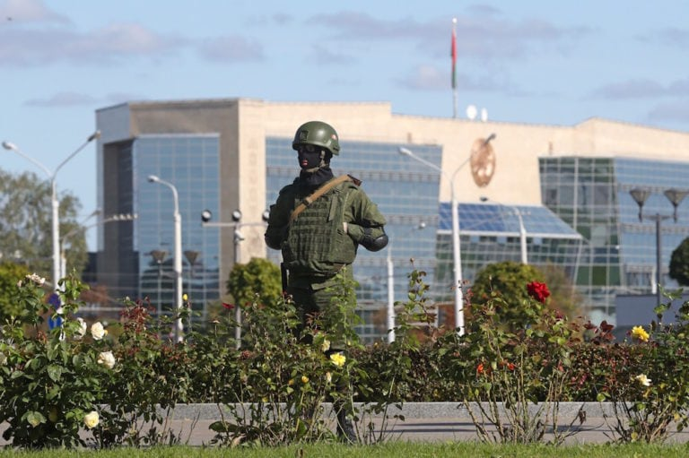 A riot police officer guards State Flag Square, with the Supreme Court building in the background, during mass protests against the presidential election results, in Minsk, Belarus, 20 September 2020, Valery Sharifulin/TASS via Getty Images