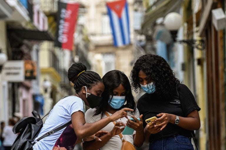 Women use their phones in a street in Havana, Cuba, 14 July 2021, YAMIL LAGE/AFP via Getty Images